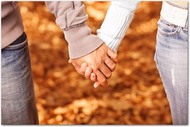 秋の紅葉の中で手をつなぐカップル