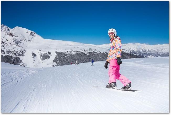 雪山で笑顔のスノボウェアの女性