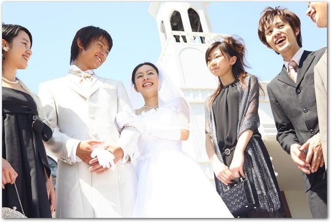 結婚式の新郎新婦と祝福する友人たち