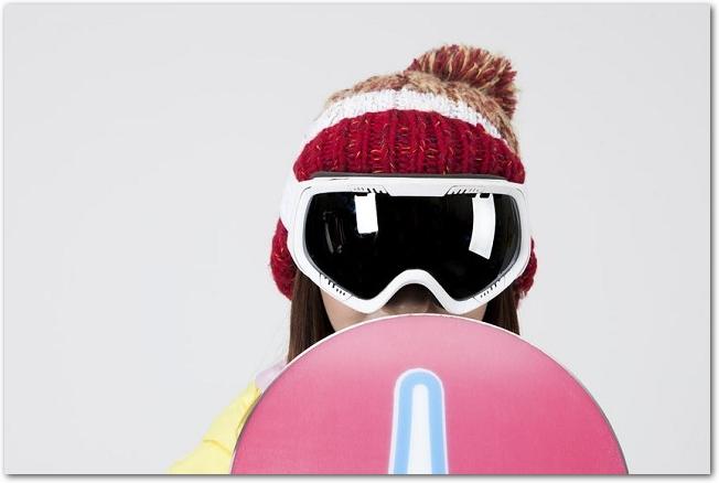 ボードに隠れているスノボウェアを着た若い女性